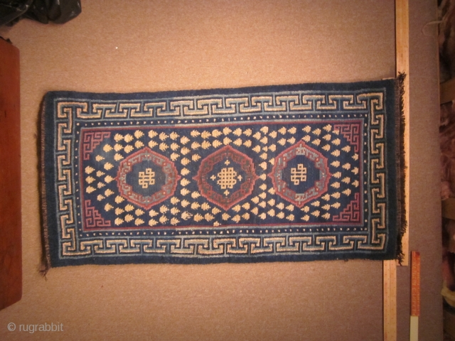Tibetan khaden, with traditional 3 coin (?gul) design and endless knots, in blue, off white and purple,c.1900, 29 by 71 inches, some reweaving at ends.