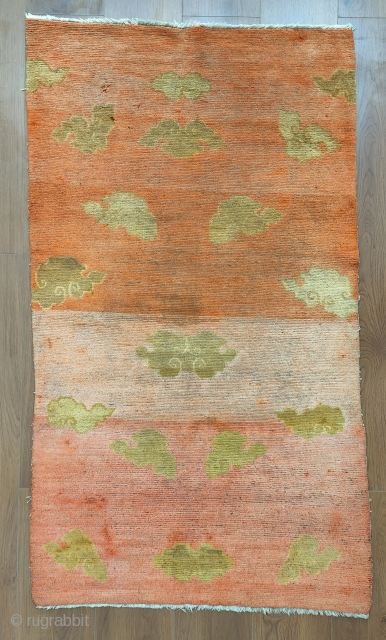 an early 20th century tibetan khaden with a rare and beautiful 17th century clouds design. the  abrashed orange background is a sythetic color, the kind of which is usually found on  ...
