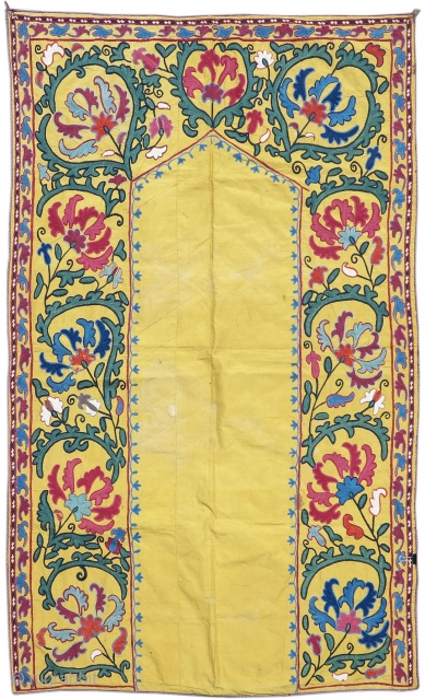 Nim suzani, 19th C (4th Q), Uzbekistan  This pleasing Central Asian embroidery,or suzani, draws a prayer niche with an open field on a golden silk ground. Stylized green foliage encapsulates artfully drawn flowers,  ...