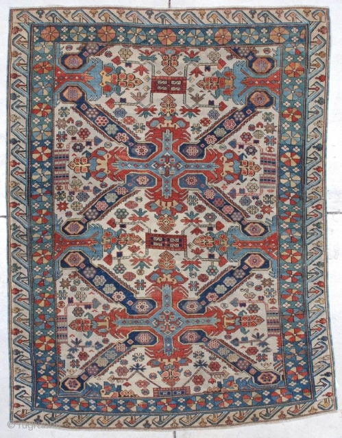 This circa 1875 Seyhore Kuba #7239 Antique Oriental Area Rug measures 4'4' x 5'8'. It has  an ivory ground with two St. Andrew Crosses in red and blue.  The interior  ...