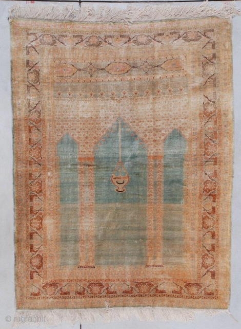 This circa 1880 silk Sivas prayer rug measures 4'2' X 5'5'. It is the coupled column variety on a turquoise ground with a nice abrash running through it.  The spandrels above  ...