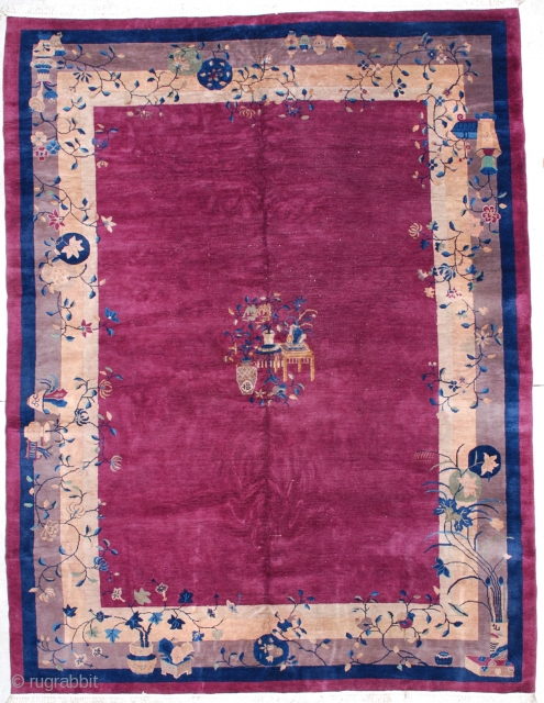 "This circa 1920 Art deco Chinese rug measures 8'10' x 11'7"". It has an urn of flowers with two tables with urns of flowers in the center of a raspberry open field,  ..."