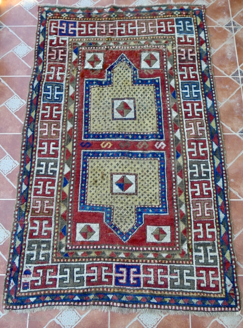 """Antique double-niche Sewan Kazak with rare """"split-shield"""" design, separated by a row of """"S""""- shaped motifs. The border design with bold, archaic """"double T"""" shaped motifs. Size:  220 x 140 cm.  ..."""