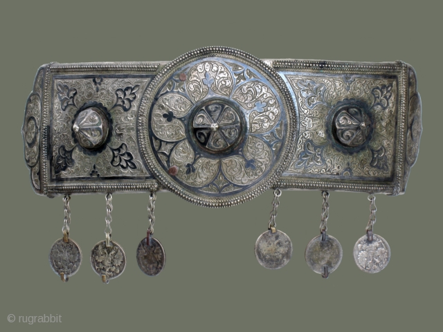 Silver Belt Buckle from Central Asia-  This handsome silver belt buckle is attractively decorated with floral patterns which are accented with 'niello' (an oxidation technique for silver). Three conical shapes provide distinctive ornamentation  ...