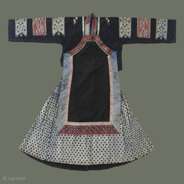 Buyi Woman's Costume - This distinctive costume is that of a married Buyi woman in Guizhou Province, SW China, and comprises a jacket, apron, and skirt. Silk embroidery and weaving, and batik  ...