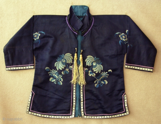 TC279  This small silk jacket was made and worn by the child of a wealthy traditional Han Chinese family. The dark blue silk fabric is embroidered on the front and back  ...