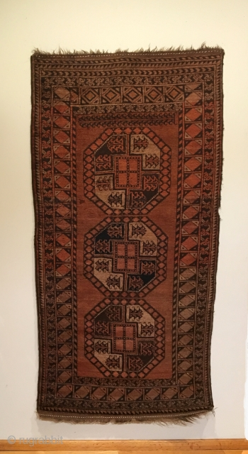 Old Afghan Qarqueen. Rich Madder-Brown abrashed field.  No secondary guls. Note: the special elongated Sulayman gul spanning top of field.  Full pile. Small bite to selvage and quarter sized moth  ...