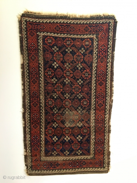 Antique Baluch Rug.  Northeast Iran.  2nd Half 19th Century.  Serrated leaves enclose stepped medallions on blue ground field.  Loss to selvage.  One area of localized wear.   ...