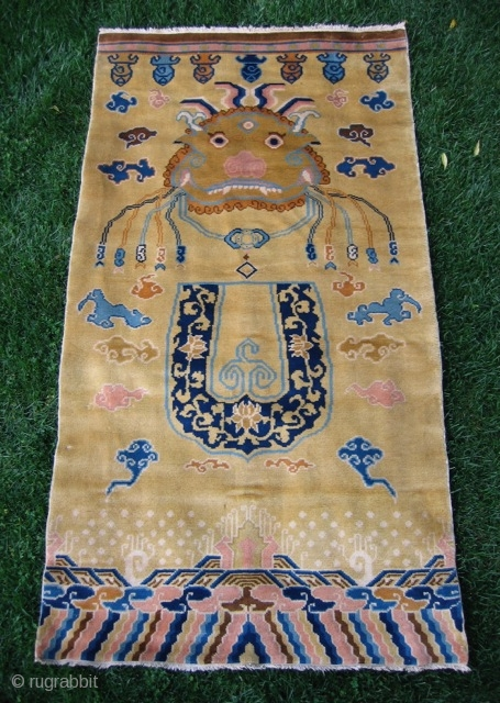 "Chinese hanging/banner rug (3' 11"" x 7' 4""); unusual t'ao-t'ieh mask design on pale gold field, full pile lustrous wool and in excellent condition; 20th century"