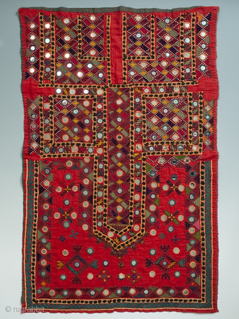 A multi-colored embroidered shirt front from the Sindh region of Pakistan. Bright red cotton is completely covered with silk and cotton thread embroidery and mirrored disks scattered throughout. In great unused condition  ...