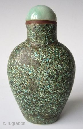 Antique Chinese Turquoise Encrusted Snuff Bottle  Antique Chinese snuff bottle of a flattened oval form with recessed foot, encrusted with finely crushed turquoise. The stopper has a jadeite lid with bright apple green  ...