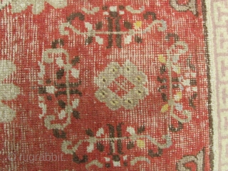 "Khotan Rug: Qing Dynasty, 19th century sitting carpet with red field and moon flower vein pattern. Lots of repair, AKA ""shabby chic""- (see enlargements). L: 125cm/49cm in and W: 64cm/25in."