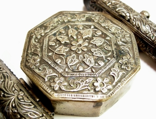 Koran Box Bazuband, British India ,19th century :   Amulet in form of two adjacent cylindrical amulet holder and an octagonal shaped Koran box. fine hammered with stylized flower decor the outsides with loops  ...
