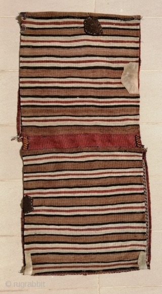 """A truly tribal Khamseh (possibility Bāsiri sub tribe) khorjin (saddlebags) from early 20th c. opened at sides. Size closed approx. 41 x 143 cm (1'4"""" x 4'9""""). Excellent shiny wool quality and  ..."""