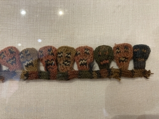 """Proto-Nazca knitted faces and figures, 11.5"""" L., mounted, in lucite display case"""