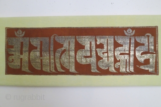 """Chinese silk panel displaying the text """"0m mani padme hum"""" (the jewel is in the lotus) in a Tibetan script with gold leaf/foil attached to a substrate of paper strips and made  ..."""