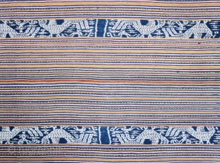 Timor | Men's cloth (beti) with ikat roosters | Indonesia  West Timor, Insana, Manufui, 1950s  Handspun cotton, natural indigo dye, warp ikat, commercial coloured thread (pinstripes), twining   Description: An elegant vintage men's cloth (beti)  ...
