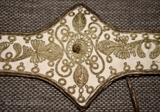 Ottoman metal embroidered felt belt. Backed with silk. With a small purse attached. Probably late 19th century. Measures 66x6cm (extends in the middle to 14cm)