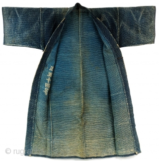"Heavy weight, densely stitched indigo dyed cotton. Tsutsugaki dyed cloth. Indigo background with red and white design on the reverse. Horizontal bands wrap around bottom of coat. Similar to reference work ""Sumi  ..."