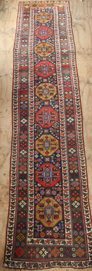 """19th century Kurdish runner with a lovely abrashed emerald green border and regular repeat yellow and red medallions on a midnight blue field. New sidecords applied and minor touches of repiling. 3'2""""  ..."""