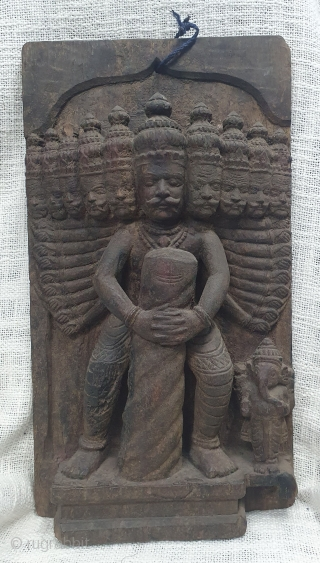 A wooden vintage decorative plaque probably a part of an architectural element showing Ravana holding a Shiva lingam with Ganesha on the side. (It is an episode from the story of Bajinath  ...