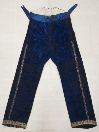 A Pair of velvet trousers in a luxurious blue colour. From Bengal.  India. Late 19th to early 20th century. The back has arrangements for suspenders with buckles made in Germany. The  ...