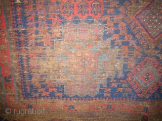 Very old Baluch main carpet, hard wear, some holes fixed with parts from old kelims, pile rugs and weft float textiles. The red colour is very good, a lot of different blue hues  ...