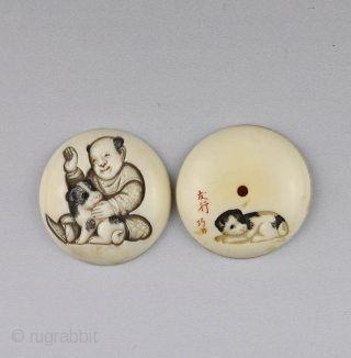 Japanese ivory manju netsuke carved in low relief  with a boy and puppy, 