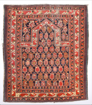 a blue-ground prayer rug from the Shirvan area showing a Marasali design of closely spaced multi-coloured botehs of highly diverse interior drawing as well as a steep mihrab. a wide border area  ...
