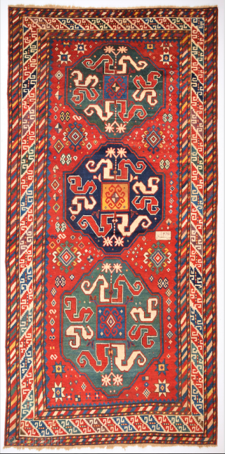 South Caucasian This red-ground Chondzoresk displays three octagonal medallions in green and dark blue, each containing eight snake motifs arranged concentrically around a box shape. The spaces not covered by the main  ...