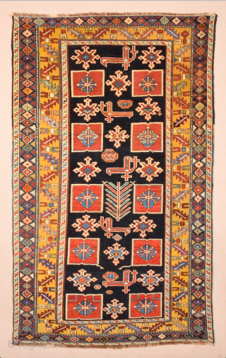 East Caucasian Karagashli Rug Ten red box shapes with a central rosette lie along the central axis of the blue field, interspersed with the abstract birds that are characteristic of the provenance;  ...