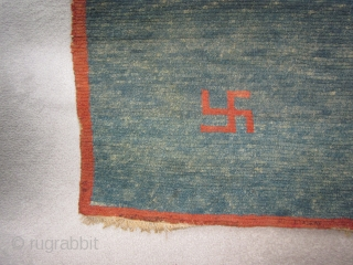 Tibetan, small khden with three eccentric swastikas, abrashed indigo ground, some repair to field,, before 1900