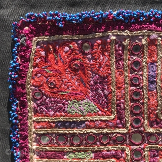Embroidered and beaded panel, probably Pashtun from Afghanistan, fine ladder stitching and gold metal threads with mirror discs, blue beads around, 24.5 cm square, probably mid-20th century, mounted on black canvas