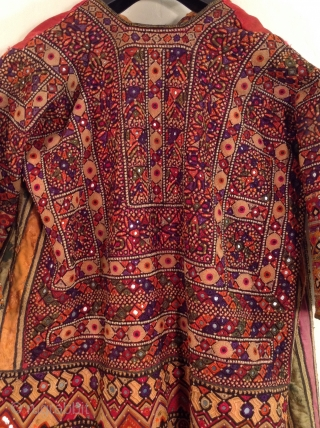 This is a wonderful embroidered dress from Rajasthan, India.  The embroidery covers all of the fabric except for the neckline and several strips of Satin fabric under the arms.  Some  ...