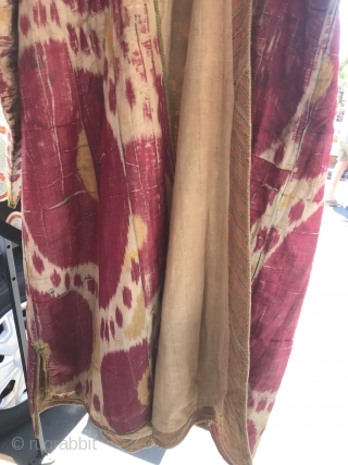 19th C. Uzbek Ikat Chapan  Polished silk heavy outerwear ikat coat. Body three colors of red, white, and yellow. Front and sleeve opening edged with hooked buta hand embroidery using colors of leaf  ...