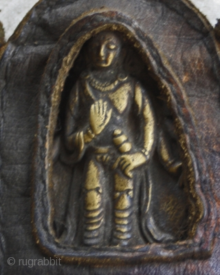 Antique Tibetan Bronze Talisman in leather case.  This antique Tibetan talisman depicts a  bronze Buddha which is also displayed in a hand sewn leather casing. The Buddha is depicted as holding a  ...