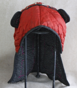EMT156   This old Chinese Miao ethnic minority child's hat is thickly padded for winter wearing. The red silk fabric with silk thread satin stitch embroidery really stands out. One silver  ...