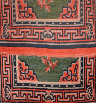 Tibetan khaden, early 1900's, with lustrous thick piled natural dyed wool sporting a central mandala-like motif with what appear to be 'leaves' spread sparingly about in a rare multi-hued green center field,  ...