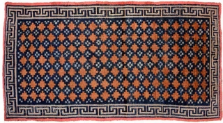 Tibetan khaden with various shades of blue making up the so-called 'gau box', or amulet, design evenly interspaced throughout the brown main field in 'lattice' like pattern. A 'Greek T' main border  ...