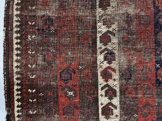 "Early Baluch rug with interesting and archaic striped or ""cane"" design. Overall very rough with areas of foundation exposed and no pile. All natural colors including an excellent saturated red. Remnant original  ..."