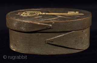 """Bentwood box, America, Wood, paint. 5.5"""" (14 cm) wide, 2"""" (5 cm) high. 19th century. Oval bentwood box with finger joint construction has a tromp l'oeil painting on a green ground. The bottom is signed Joe Watson  ..."""