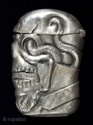 """Match safe, Unknown manufacturer. Sterling silver. 2.5"""" (6.3 cm) high. c. 1895. This rare match safe is marked STERLING and there is a pinched striker on the bottom. A serpent winds through a dapper skull's sye sockets,  ..."""