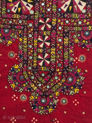 An embroidered shirt front from the Sindh region of Pakistan. Deep red cotton with some tie-dyed dots covered with silk thread embroidery and mirrored disks scattered throughout. In great condition with all  ...