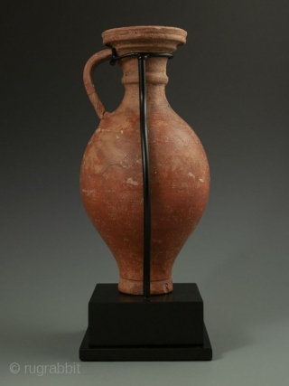 Antique Roman Vase with Stand  Red clay Roman pottery vessel with handle, flanged lip over curved body, worn white design, most likely a wine ewer, display stand.  Provenance Handley Collection   Date 300 AD   Size  ...