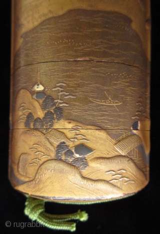 Antique Japanese Gold Landscape Inro Japanese gold lacquer inro with five compartments, decorated in low relief landscape scene of lakeside mountains, cottages, pagodas, pine trees, and bridges in gold lacquer and accents of  ...