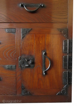 Antique Japanese Keyaki Front Tansu   Unusual Japanese single section isho tansu (clothing chest), with dramatic Keyaki (elm) front drawers, opened by simplistic hirute style handle pulls and small, squared locks. Its bottom safe  ...