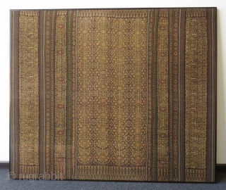Indonesian Framed Ikat Sarong Woman's Skirt  A framed Indonesian sarong, a long cloth worn as a wrap skirt, hand-woven with bands of intricate scrolls and medallion repeats. Made of warp irate, with natural  ...