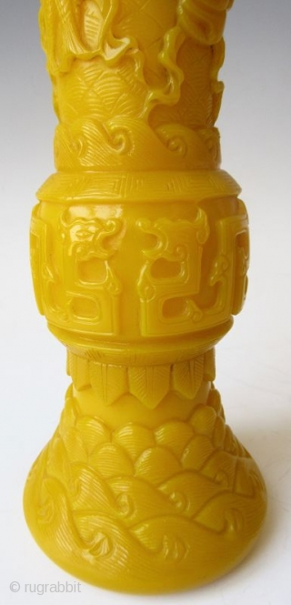 Antique Chinese Pair of Yellow Peking Glass Gu Vases  An elegant pair of Chinese monochrome yellow peking glass gu vases with relief carvings of waves, archaic scrolling serpents, one vase with a pair  ...