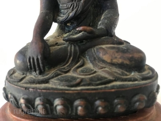 19th Century Sino Tibetan Seated Buddha  Bronze Buddha from Sino Tibetan tradition. Wonderful details on the robe with inscription on back. Buddha sits on a wooden stand. Provenance: From the William Ashby Estate.  ...